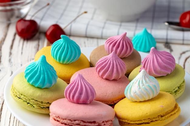 Franse macaronkoekjes van heldere kleuren die in witte ceramische plaat worden gediend