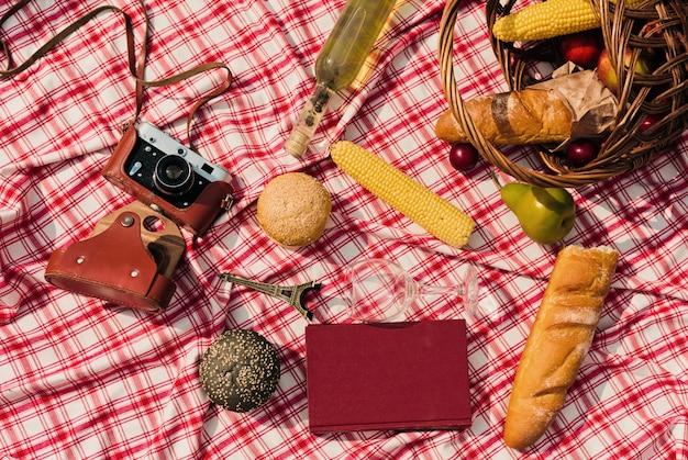 Franse mand met fruit, stokbrood, boek, retro camera op een geruite rode tafellaken buitenshuis
