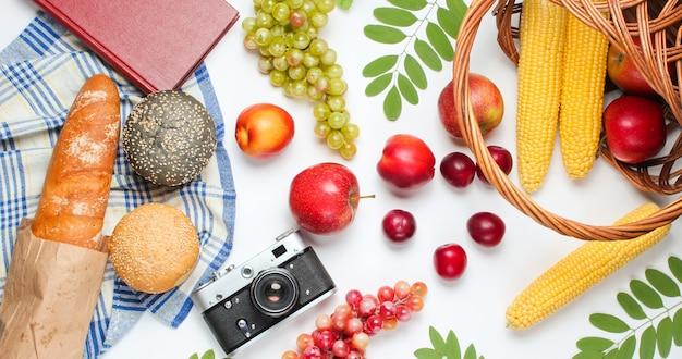 Franse picknick in retrostijl. mand met groenten en fruit, retro camera, boek, stokbrood en andere picknick eten witte achtergrond. bovenaanzicht. studio opname