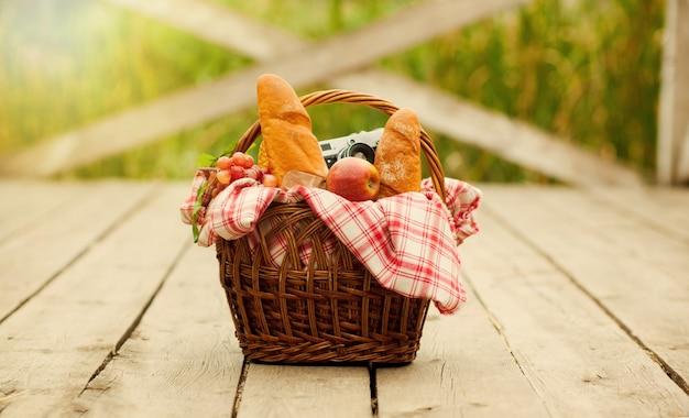 Franse provinciale picknick. retro-stijl picknickmand met voedsel, retro camera op houten pier aan het meer buiten