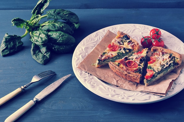Franse quiche met eieren, verse spinazie, tomaten en spek