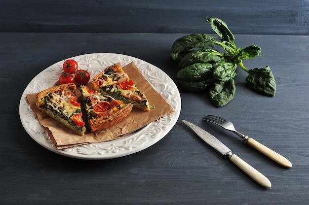 Franse quiche met eieren, verse spinazie, tomaten, spek