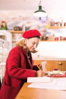Franse schrijver. elegante franse schrijver met rode baret die inspiratie heeft tijdens het werken in de bakkerij