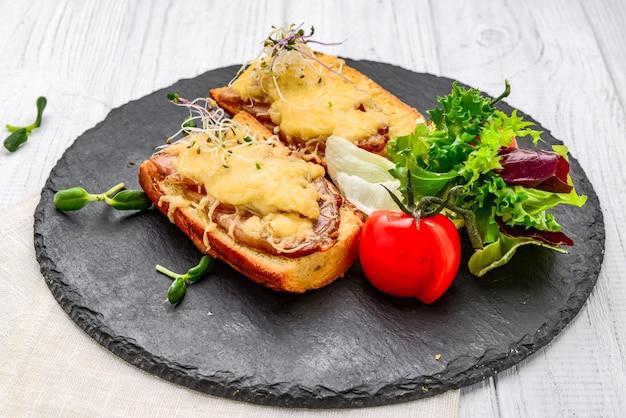 Franse toast ham kaas en salade op schotel. op de houten tafel