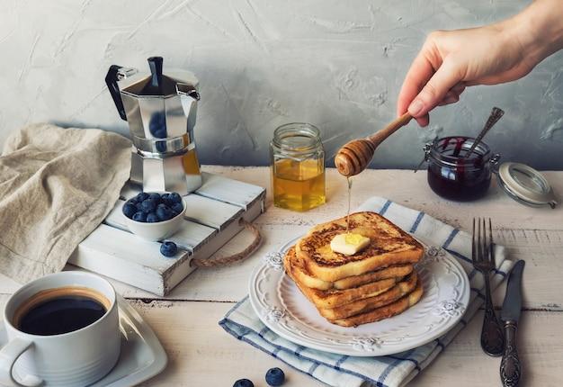Franse toast met boter en bosbessen als ontbijt. de hand giet honing op de bovenkant.
