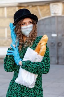 Franse vrouw in hoed, medisch masker en rubberen handschoenen op straat met stokbrood glimlacht door beschermend masker