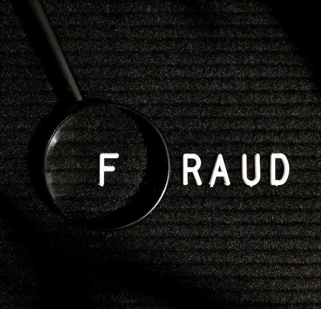 Fraude woord met letter in een vergrootglas bovenaanzicht