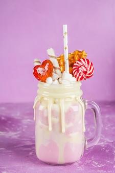 Freakshake van roze smoothie, room. monstershake met lolly's, wafels en marshmallow.