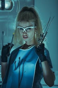 Freaky woman doctor met enge medische hulpmiddelen in bloedige doek kijkend naar de camera in een donker kliniekkantoor