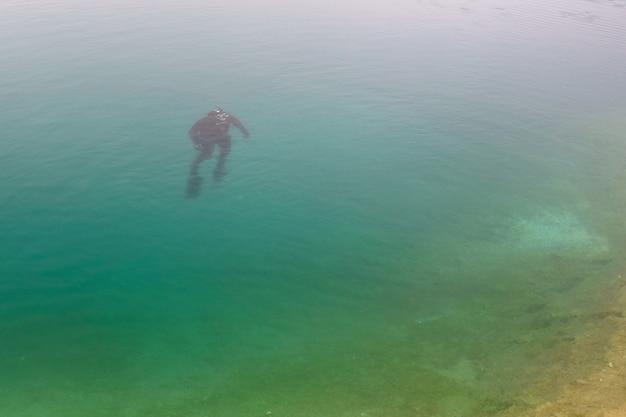 Freediver die omhoog in het blauwe water drijft