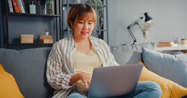Freelance aziatische dame vrijetijdskleding met behulp van laptop online leren in de woonkamer thuis