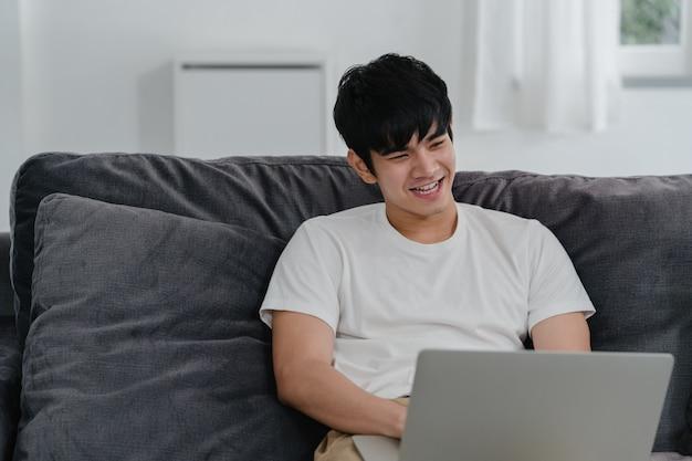 Freelance aziatische man aan het werk thuis, mannelijke creatief op laptop op sofa in de woonkamer. de ondernemer van de bedrijfs jonge menseneigenaar, speelt computer, die sociale media op werkplaats controleren bij modern huis.