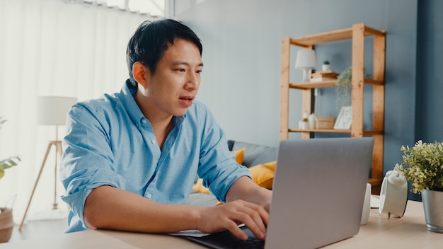 Freelance aziatische man vrijetijdskleding met behulp van laptop online in de woonkamer op kantoor aan huis