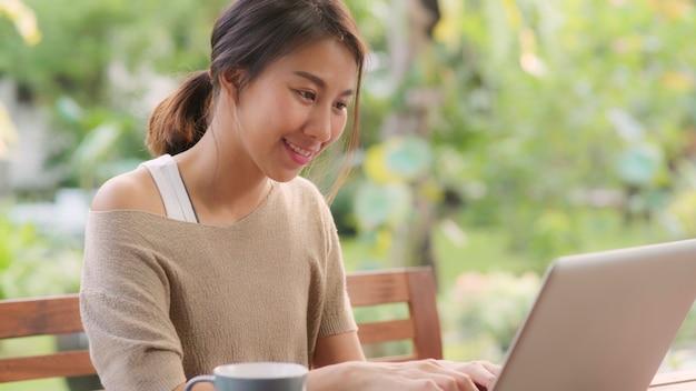 Freelance aziatische vrouw die thuis, bedrijfswijfje werkt dat aan laptop zitting op lijst in de tuin in ochtend werkt. lifestyle vrouwen werken thuis concept.
