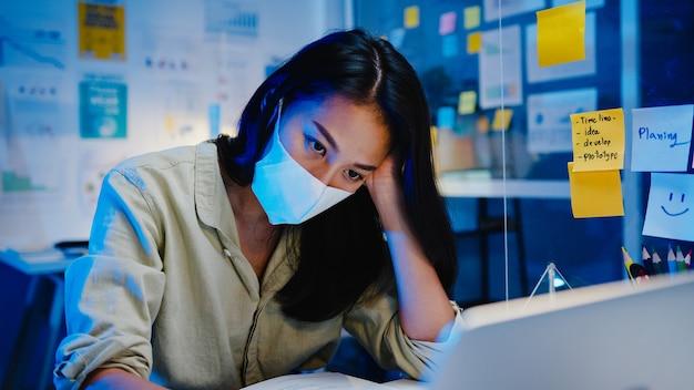 Freelance aziatische vrouwen dragen een gezichtsmasker terwijl ze laptop hard werken op een nieuw normaal kantoor. overbelasting van huis 's nachts, zelfisolatie, sociale afstand nemen, quarantaine voor coronaviruspreventie.