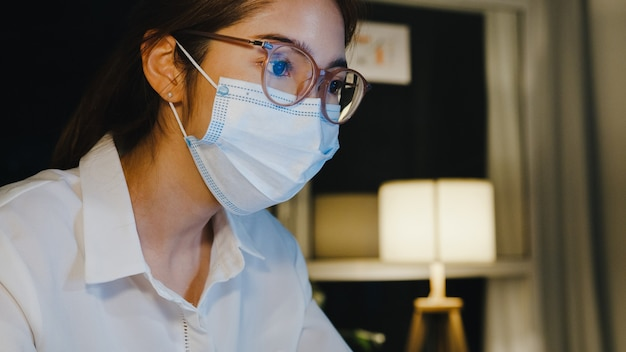 Freelance azië-dame draagt een medisch gezichtsmasker en gebruikt laptop hard werken in de woonkamer thuis.