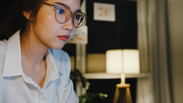 Freelance azië dame met behulp van laptop hard werken in de woonkamer thuis.