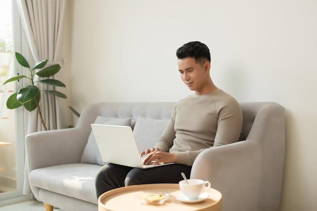 Freelance carrière. glimlachende man aan het werk op laptopcomputer zittend op de bank thuis.
