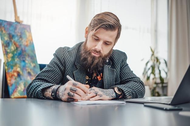 Freelance en remote werken. binnenlandse levensstijl van een serieuze man met een baard, hij doet papierwerk aan tafel met een laptop en smartphone.