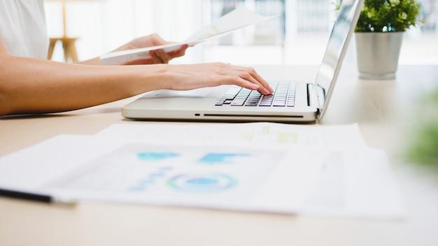 Freelance jonge aziatische zakenvrouw vrijetijdskleding met behulp van laptop die in de woonkamer thuis werkt.