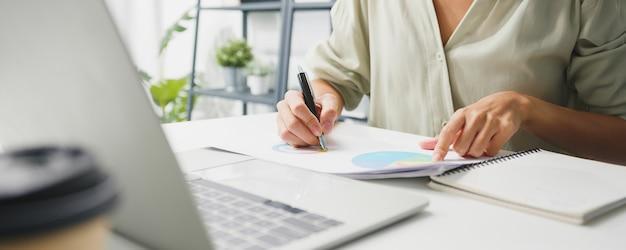 Freelance jonge zakenvrouw vrijetijdskleding met behulp van laptop die in de woonkamer thuis werkt.
