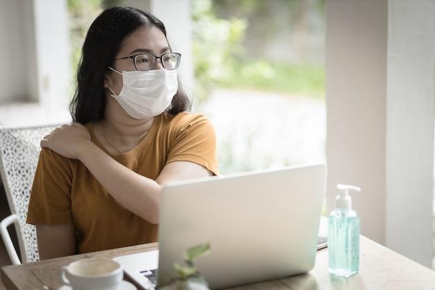 Freelance mensen zakelijke vrouw met beschermend masker casual lijdt aan schouderpijn door werken met een laptop, thuiswerken, concept van preventie van de verspreiding van het covid-19-virus