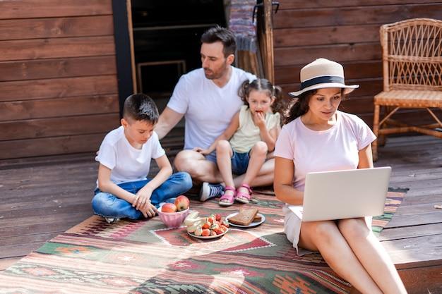 Freelance moeder werkt met een laptop zittend op de veranda tijdens een familievakantie, op de achtergrond haar man en twee kinderen die niet erg blij zijn met het gebrek aan aandacht van moeder