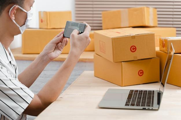 Freelance ondernemer man bereid kartonnen pakketdoos en product klaar voor levering.