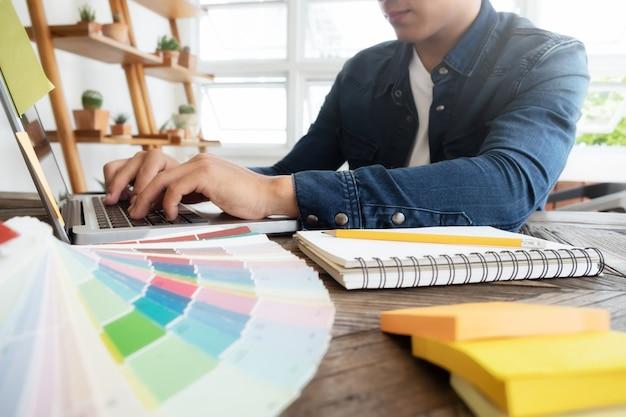 Freelance photo editor, kunstenaar, grafische ontwerper die aan bureau werkt in creatief kantoor. kunstenaar tekenen iets op grafische tablet op kantoor.