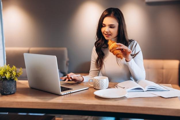 Freelance student vrouw met behulp van laptop terwijl u thuis zit. jonge vrouw zitten in de keuken en online werken op laptop. mooie vrouw thee koffie drinken tijdens het werken.