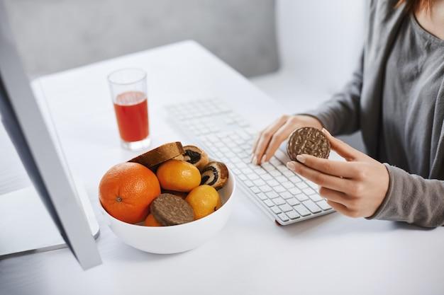 Freelance thuiswerken en een hapje eten. bebouwd portret van vrouw voor computer, die koekje houdt en informatie met toetsenbord typt, dichtbij fruitmand zit en sap drinkt