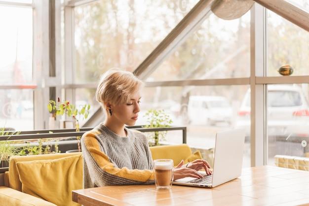 Freelance vrouw die met laptop in koffiewinkel werkt