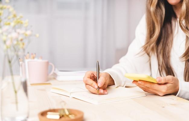 Freelance vrouw met laptop en kopje koffie met behulp van mobiele telefoon en online winkelen, zittend op de bank. gelukkig meisje woking vanuit kantoor aan huis. afstandsonderwijs online onderwijs en werk.