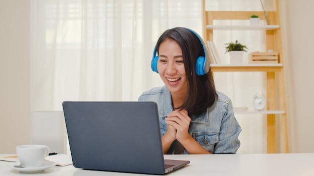 Freelance zakelijke vrouwen vrijetijdskleding met behulp van laptop werkgesprek videoconferentie met klant op de werkplek in de woonkamer thuis. het gelukkige jonge aziatische meisje ontspant het zitten op bureau doet werk in internet.