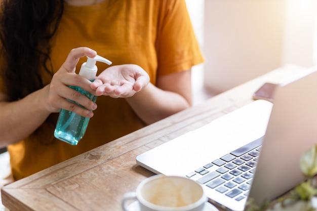 Freelance zakenvrouw met behulp van hand zetten ontsmettingsmiddel bij de hand voor het reinigen van de hand om virussen te voorkomen en het werken met laptop