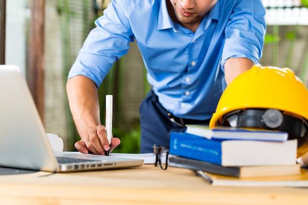 Freelancer - architect die thuis aan een ontwerp of ontwerp werkt, op zijn bureau liggen boeken, een laptop en een helm of helm
