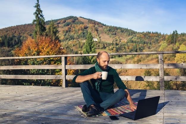 Freelancer bebaarde man zit op het terras in de bergen met laptop, smartphone en drinkt koffie.