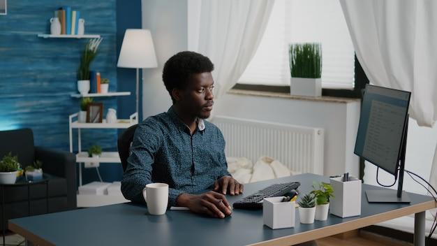 Freelancer die aantekeningen maakt op kladblok en in de computer kijkt