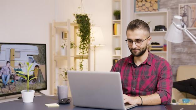 Freelancer die een slokje koffie neemt terwijl hij op een laptop in de woonkamer werkt. vriendin op de achtergrond kijkt tv.