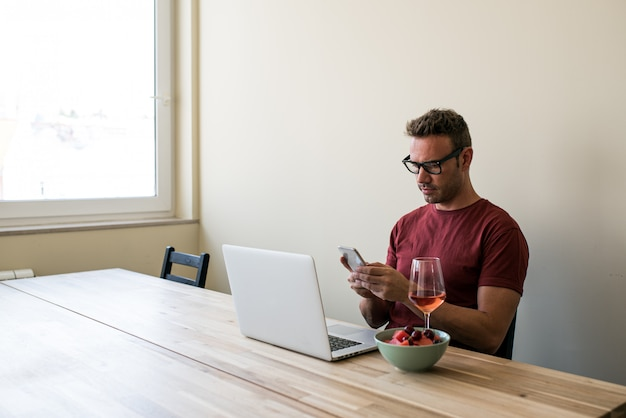 Freelancer die laptop en mobiele telefoon thuis gebruikt