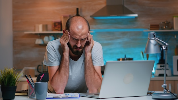 Freelancer die lijdt aan hoofdpijn die de tempel aanraakt na uren werken op een laptop thuis in de moderne keuken. drukke gefocuste werknemer met behulp van moderne technologie netwerk draadloos overuren werken