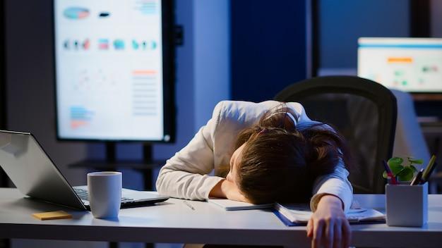 Freelancer die overwerkt aan project dat op het bureau in slaap valt met de hand op financiële documenten die de deadline proberen te respecteren. werknemer met behulp van moderne technologie netwerk draadloos, slapen op tafel.