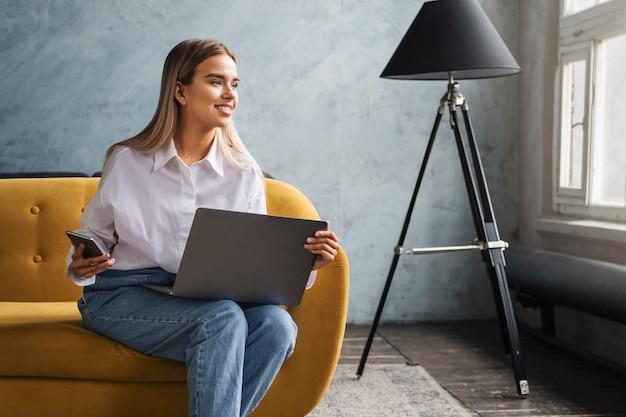 Freelancer doet projecten vanuit huis, met behulp van aangesloten apparaten en internettoegang.
