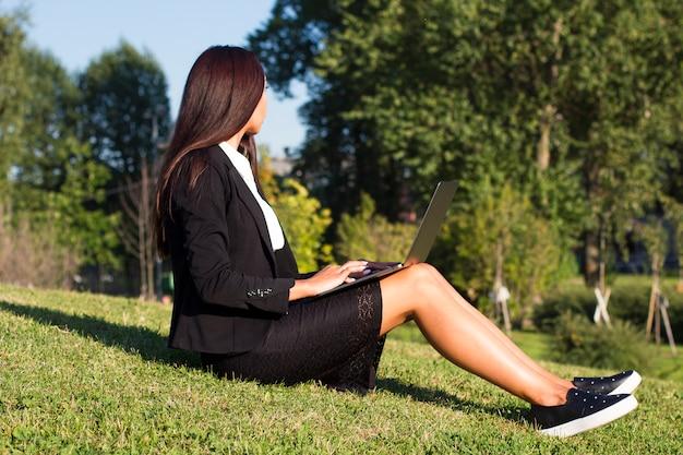 Freelancer formeel gekleed meisje in pak werkt buiten aan haar laptop, zittend op het gras op een zonnige zomerdag. freelance werkconcept. onherkenbaar persoon, vrouw.