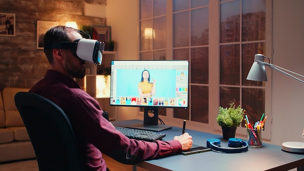 Freelancer-fotograaf die een virtual reality-headset gebruikt terwijl hij 's nachts foto's retoucheert met een grafisch tablet in een thuiskantoor.
