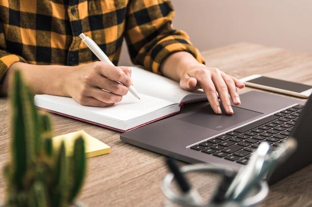 Freelancer in geel shirt maken van aantekeningen in zijn notitieblok tijdens het navigeren op internet