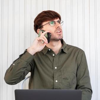 Freelancer in gesprek met zijn cliënt aan de telefoon