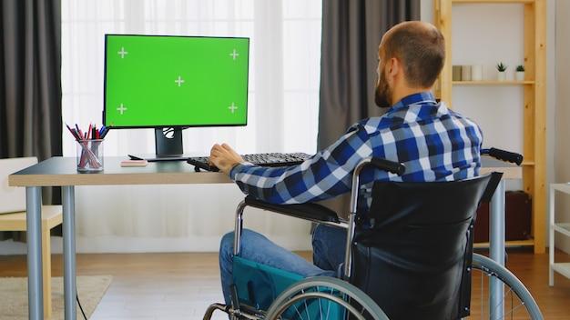 Freelancer in rolstoel typen op computer met groen scherm vanuit kantoor aan huis.