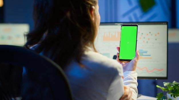 Freelancer kijkt naar mobiele telefoon met groen scherm tijdens videovergadering die 's avonds laat aan het bureau in het kantoor zit. zakenvrouw kijken naar desktopmonitor met groene mockup, chromakey