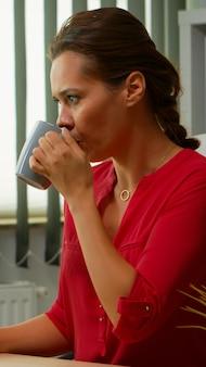 Freelancer koffie drinken op kantoor en typen op computer in speciaal programma. ondernemer die werkt in een moderne professionele werkruimte in een zakelijk bedrijf met een draadloos computertoetsenbord